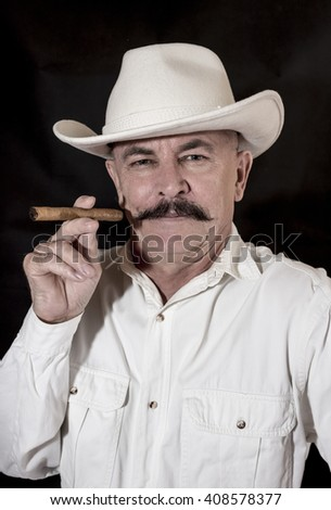 The cowboy with mustache in a white hat, smoking a cigar - stock photo