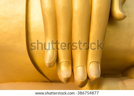 the finger tip of gigantic outdoor golden Buddha image in Thailand - stock photo