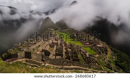 the foggy ruins of machu picchu - long exposure including fog movement - stock photo