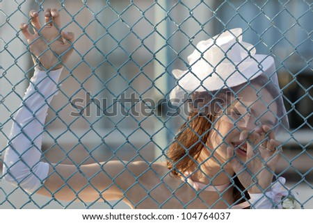 The girl in a white dress behind a fence - stock photo
