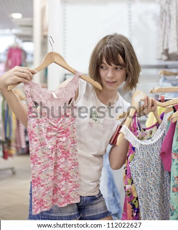 The girl in shop tries on clothes - stock photo