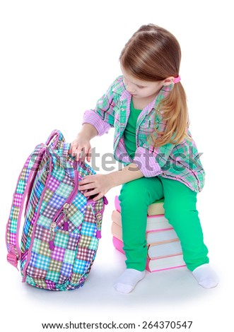 The girl opens a school backpack - isolated on white background - stock photo