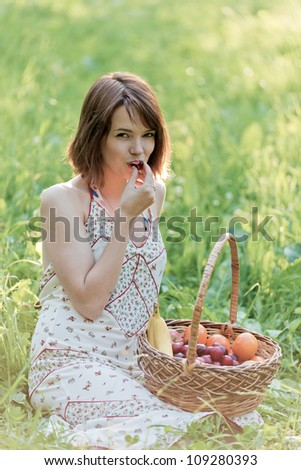The girl sits on a glade and eats a sweet cherry - stock photo