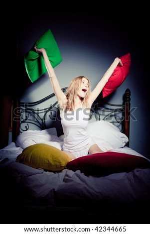 The girl throws up pillows - stock photo