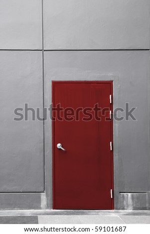 the gray wall with the red door - stock photo