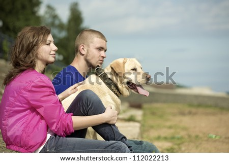 The guy, the girl and dog sit on a beach - stock photo