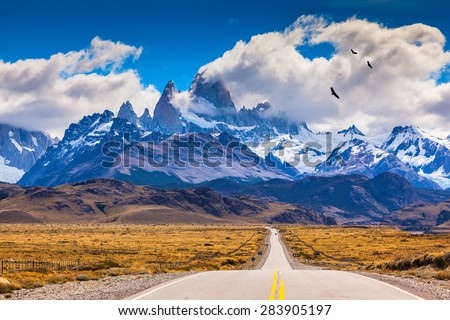 The highway crosses the Patagonia and leads to snow-capped peaks of Mount Fitzroy. Over the road flying flock of Andean condors - stock photo