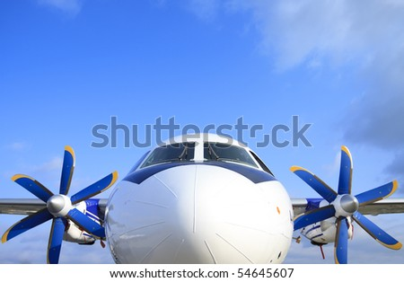 The passenger plane with blue and yellow propeller - stock photo