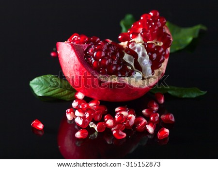 the pomegranate with leaves on black background - stock photo
