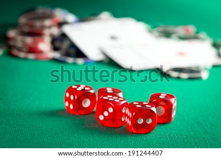 the red casino dice and casino chips on green table - stock photo