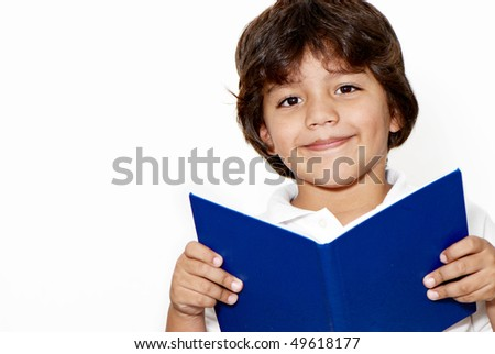 The schoolboy with the book in hands on a light background - stock photo