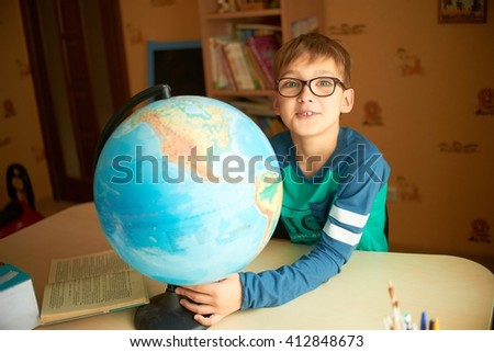 the student studies the globe. Schoolboy with globe. boy with globe - stock photo