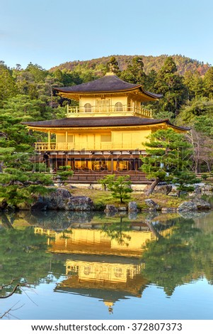 The Temple of the Golden Pavilion in Kinkaku-ji temple, Kyoto, Japan. This magnificent temple is surrounded by a pond and the highest floors are covered with gold panels. - stock photo