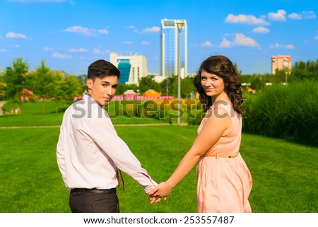 The young happy couple walking in the city park on grass and holding hands in summer. - stock photo