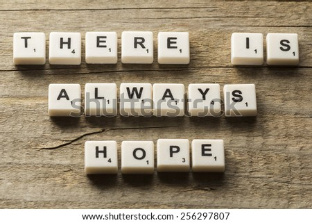 """""""There is always hope"""" text on a wooden background - stock photo"""