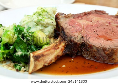 thick juicy portions of grilled fillet steak served with green vegetables on a white plate - stock photo