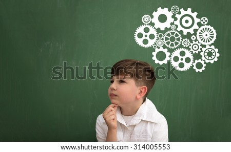 Thinking schoolboy with brainstorming shown through the mechanism of gear on blackboard - stock photo