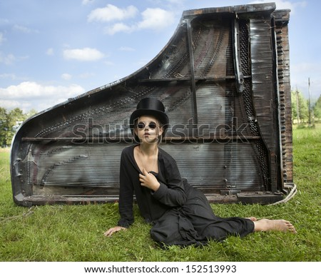 Thoughtful girl in black glasses and hat sitting on the green grass in front of oprakinutym old royalem6opktannym covered with dust and cobwebs. - stock photo