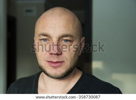 Thoughtful man in the interior of his house - stock photo