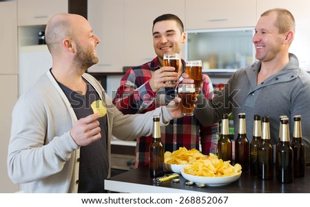 Three american men drinking beer and laughing at house party - stock photo