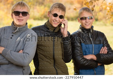 Three guys in autumn jacket and sunglasses, two of the boys twin brothers. Image with Instagram-like filter - stock photo