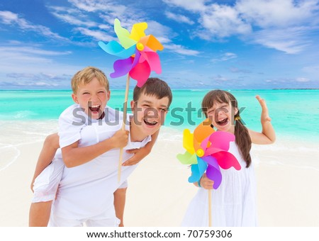 Three happy children with colorful windmills on tropical beach, blue sky and cloudscape background. - stock photo