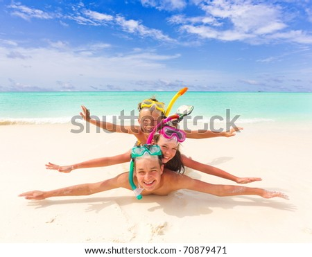 Three happy children with snorkels pretending to swim on sandy tropical beach, sea and blue sky background. - stock photo