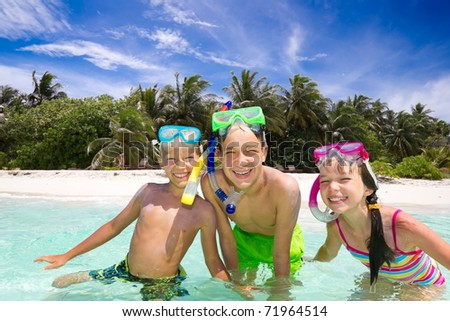 Three happy young children with snorkels playing in sea, tropical beach in background. - stock photo