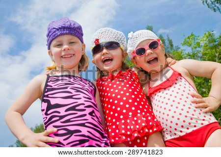 three little girls playing on the beach in a swimsuit - stock photo