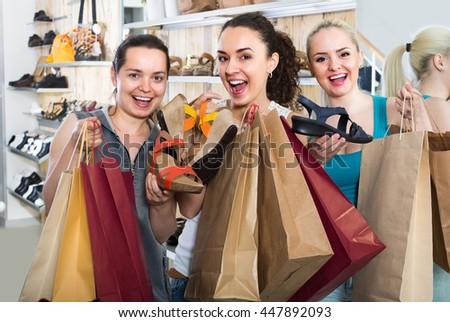 Three young cheerful girls shopping together and chatting  indoors - stock photo