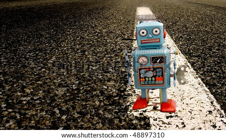 tin robot on a long road - stock photo