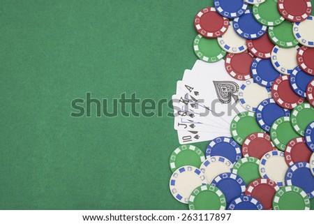 10 to Ace spade straight flush of pokers and lots of chips on casino table with copy space - stock photo