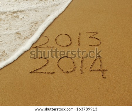 2013 to 2014 new year sign written in sand with waves lapping at the edge, symbolising change of year - stock photo