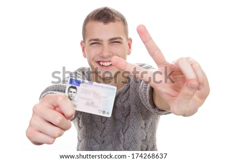 16 to 18 year old boy just received his driver license - stock photo