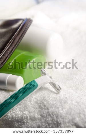 toilet bag with set of cosmetics and razor in different positions - stock photo