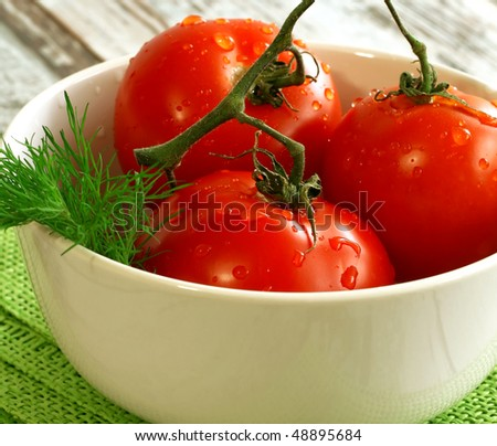 tomatoes with water drops in bowl - stock photo