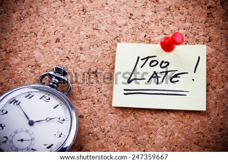 """""""Too late!"""" written on a post note and hanged on the cork-board with an old pocket watch. - stock photo"""
