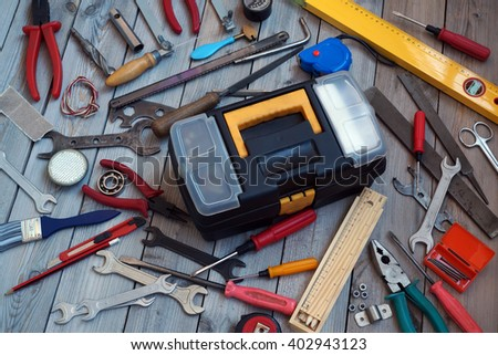 Tool box and tools scattered around him on the wooden floor, top view. Locksmith and carpentry tools.                            - stock photo