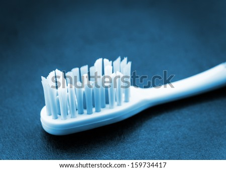 Toothbrush on dark surface. Blue toned image. - stock photo