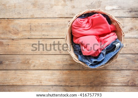 Top view Clothes in a laundry basket on Wood floor - stock photo