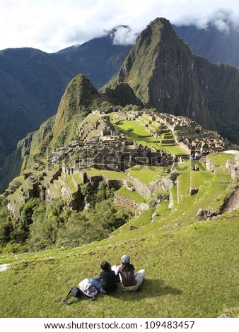 2 tourists looking at the mysterious city of Machu Picchu, Peru - stock photo