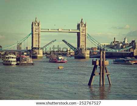 Tower Bridge raised over River Thames. London, England, Retro filtered image. NB logos etc removed. - stock photo