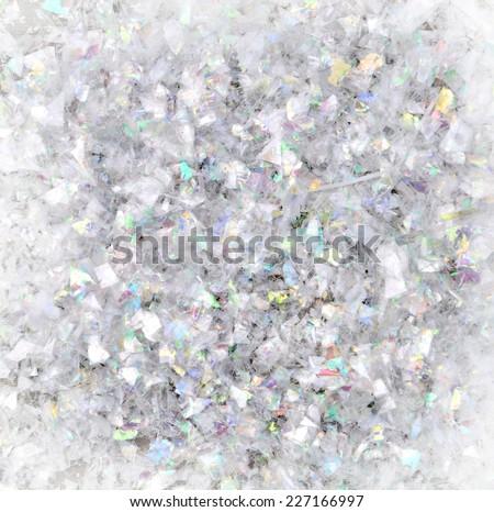 transparent plastic confetti reflecting some colors - stock photo