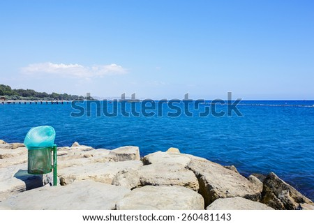 Trash basket can near the sea beach. Littering the beach and the sea. Clean environment.  - stock photo