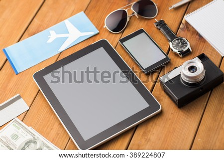 travel, tourism, technology and objects concept - close up of smartphone with tablet pc computer, airplane ticket and personal stuff - stock photo