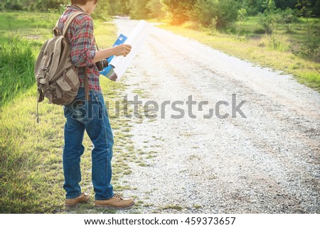Traveler man with backpack looking at  map. Said view tourist traveler on The road in the forest vacation concept vintage tone - stock photo
