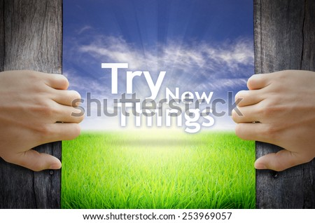 """""""Try new things"""" Motivational quotes. Hands opening a wooden door then found a texts floating among new world as green grass field, Blue sky and the Sunrise. - stock photo"""
