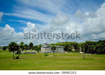"""Tulum at midday under a bright cloudy sky when the grass is green and the cumulus clouds are puffy and low in the sky made up of fascinating patterns - stock photo"