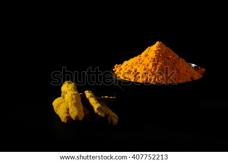 Turmeric powder and roots or barks in black bowl on black background - stock photo