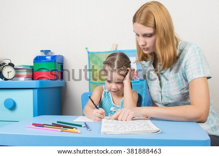Tutor teaches the child to write letters - stock photo